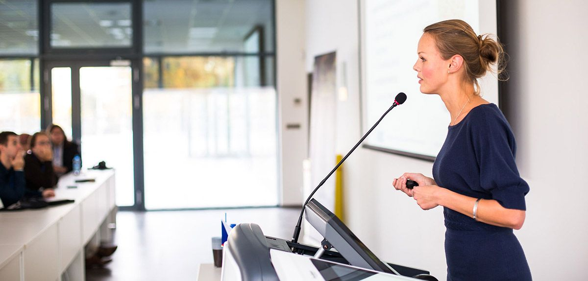 Woman speaking a podium.