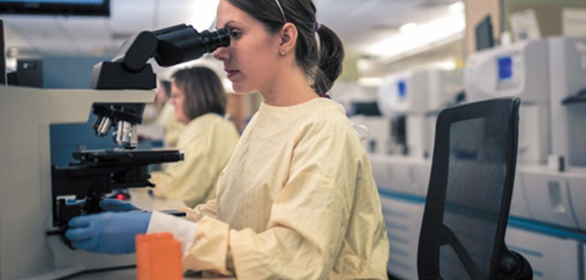 Woman looking in to a microscope wearing scrubs.