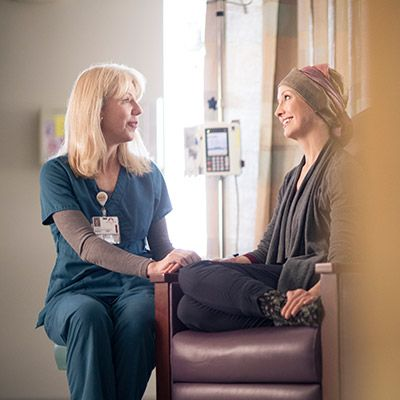 Nurse talking to a patient during her treatment.