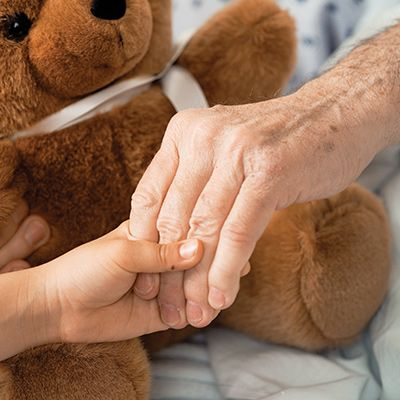 Child holding adult's hand over a teddy bear.