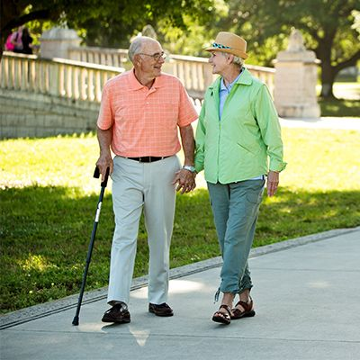Man with a cane taking a walk with his wife.