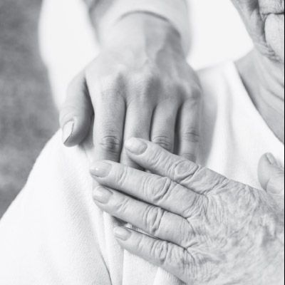 Elderly patient with placing hand over another hand on their shoulder.