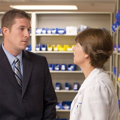 pharmacist talking with man in suit in front of pharmacy shelves