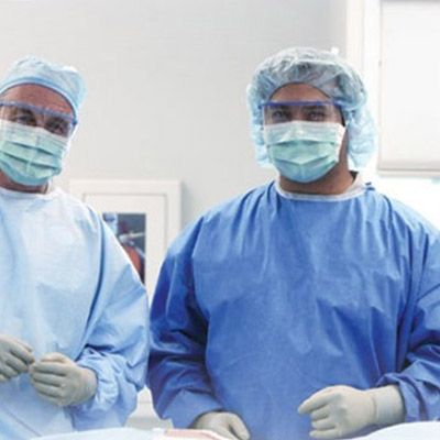 Two surgeons in protective gowns, masks, caps and gloves.