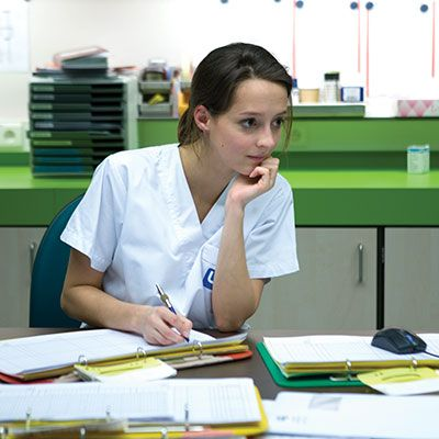 Nurse in nurses station writing on paper.