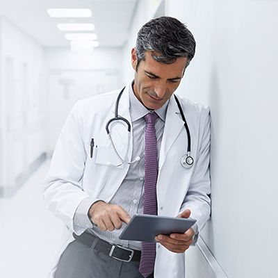 Physician leaning against a wall looking at a tablet