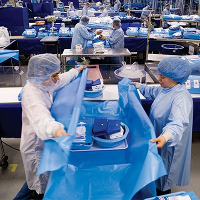 Several medical professionals in protective caps and gowns assembling and wrapping Presource kitting.