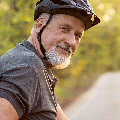Older man up close with gray hair and beard, wearing bicycle helmet.