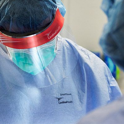 Surgeon wearing facemask and surgical gown.