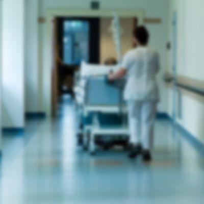 Nurse pushing a hospital bed.