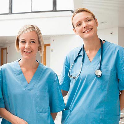 Two nurses in blue, one wearing a stethoscope.