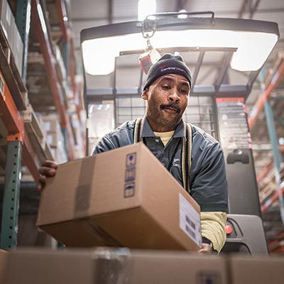 Warehouse worker stacking boxes.