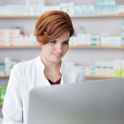 pharmacist using computer, standing in front of shelves