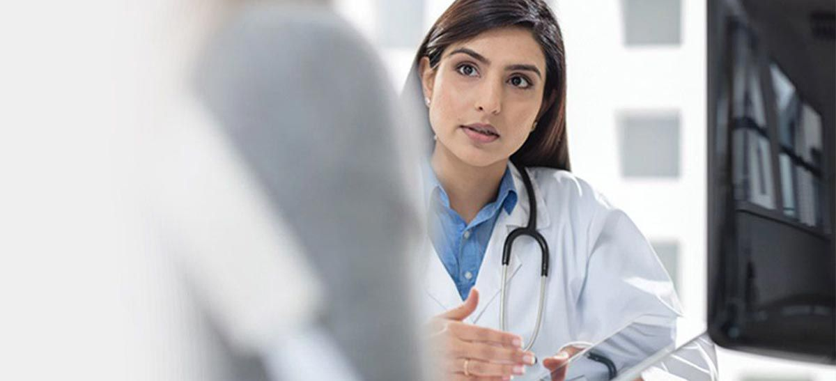 Doctor wearing a stethoscope talking with a patient.