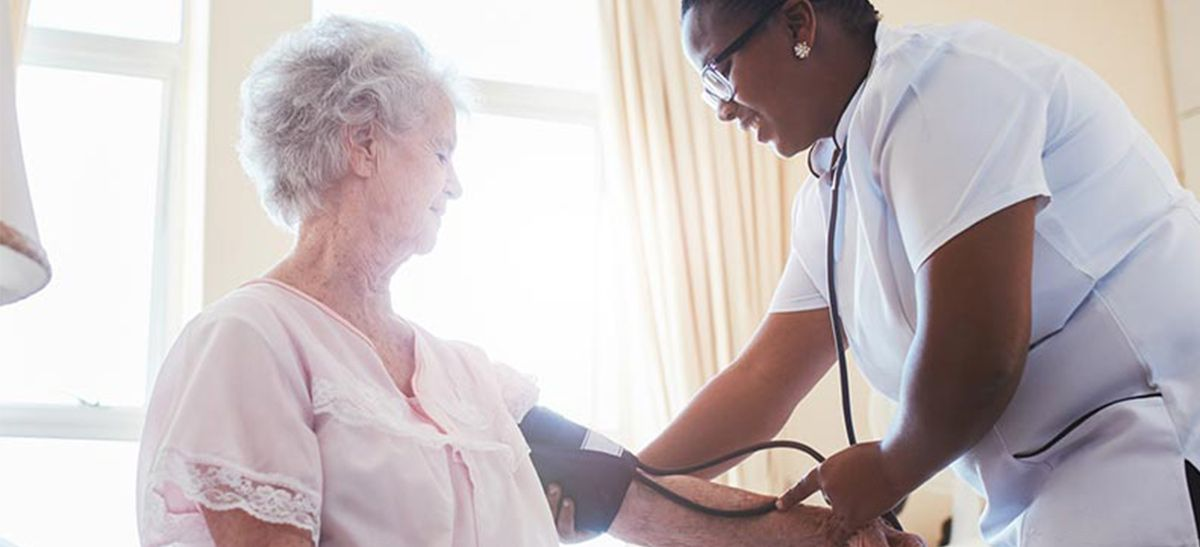 Nurse checking a patient's blood pressure at home.