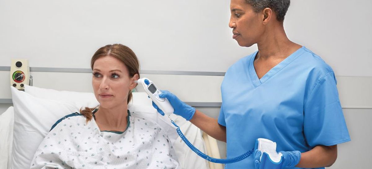 Nurse taking a patient's temperature in her ear.