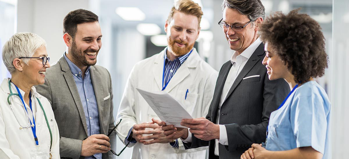Group of medical professionals reading a paper.