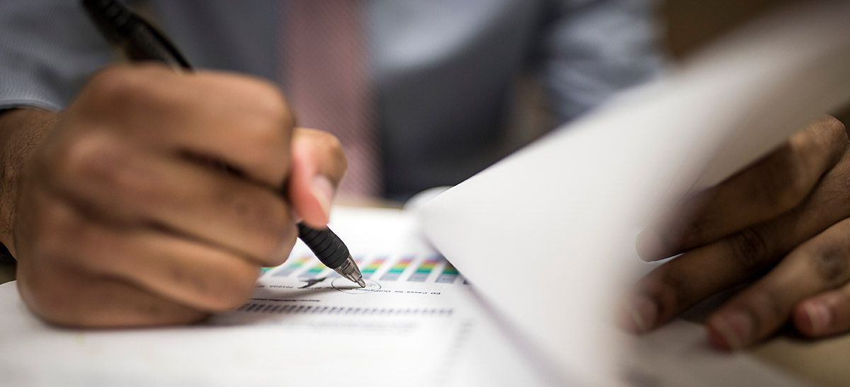 Closeup of man holding a pen and writing on printed charts.