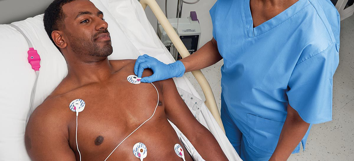 Nurse placing electrodes on a patient's chest.