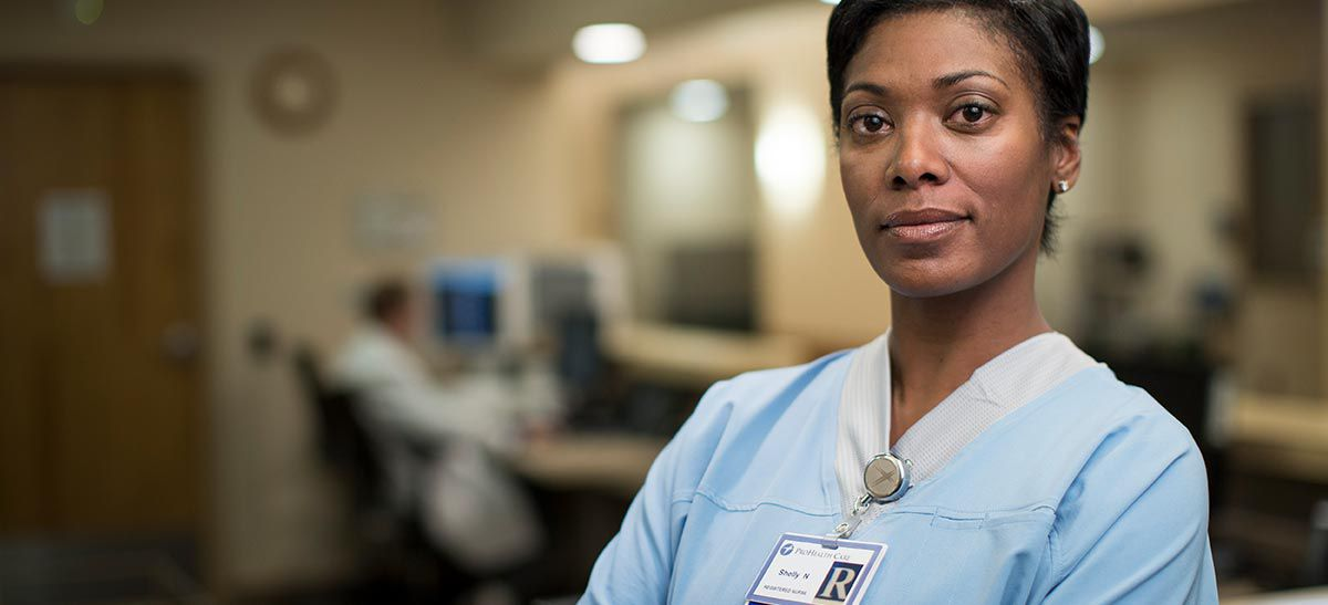 nurse in blue scrubs with RN name badge.
