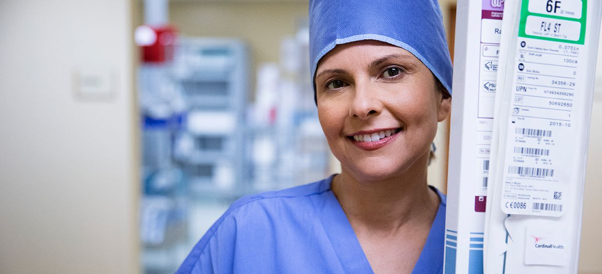 Nurse in surgical cap holding products.