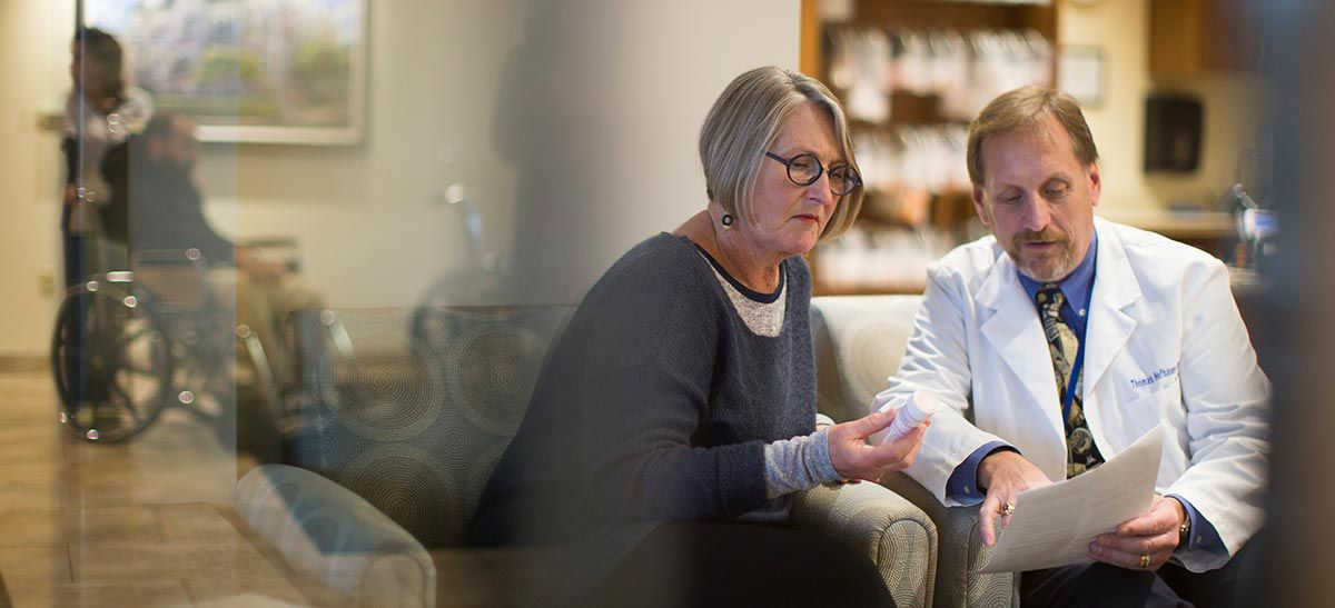 Pharmacist consulting with a patient in the hospital lobby.