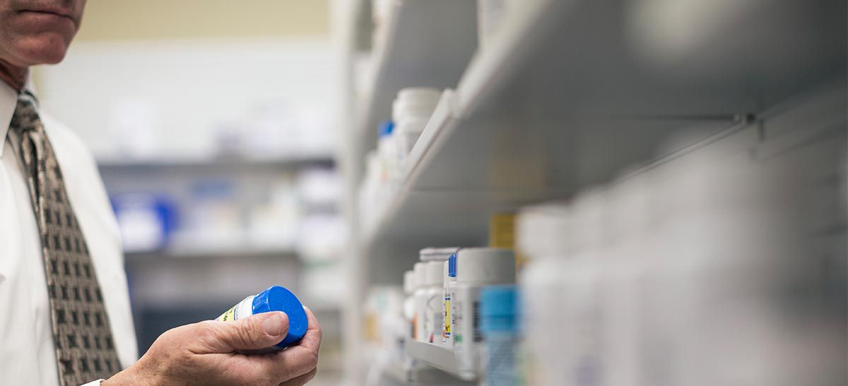 Pharmacist pulling medication bottle from shelf to fill a prescription.