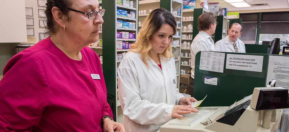 Pharmacy tech and pharmacist behind the counter.