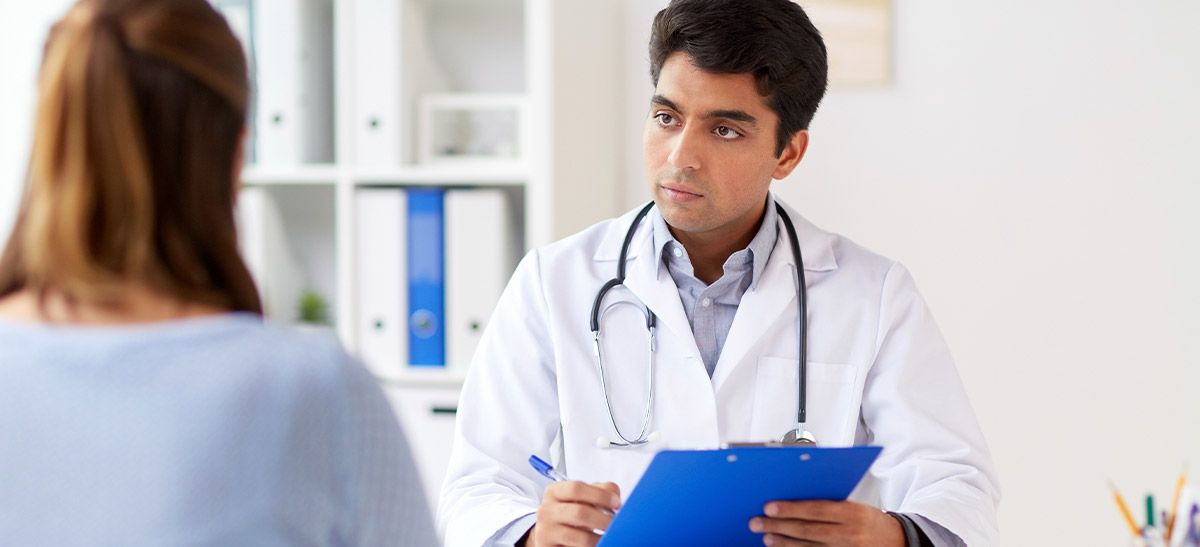 Physician speaking to patient, holding clipboard.