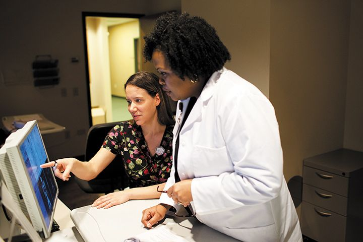 Nurse pointing out something on the computer to a doctor.