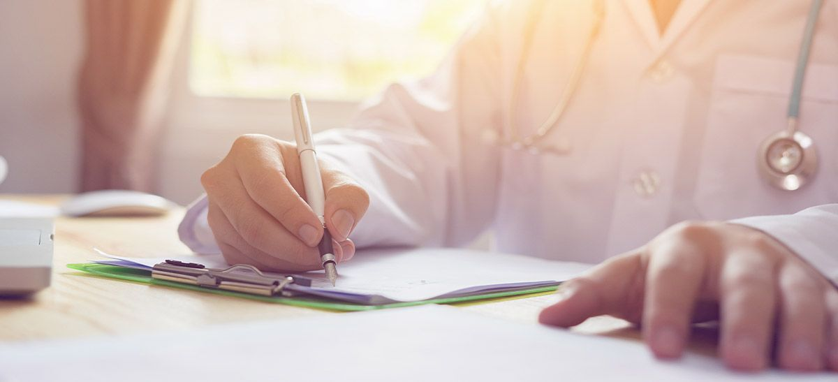 Physician writing on clipboard.