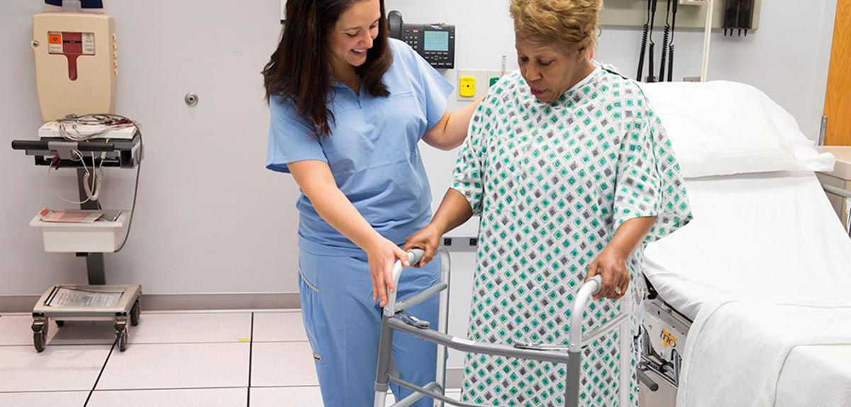 Nurse helping a patient with a walker.