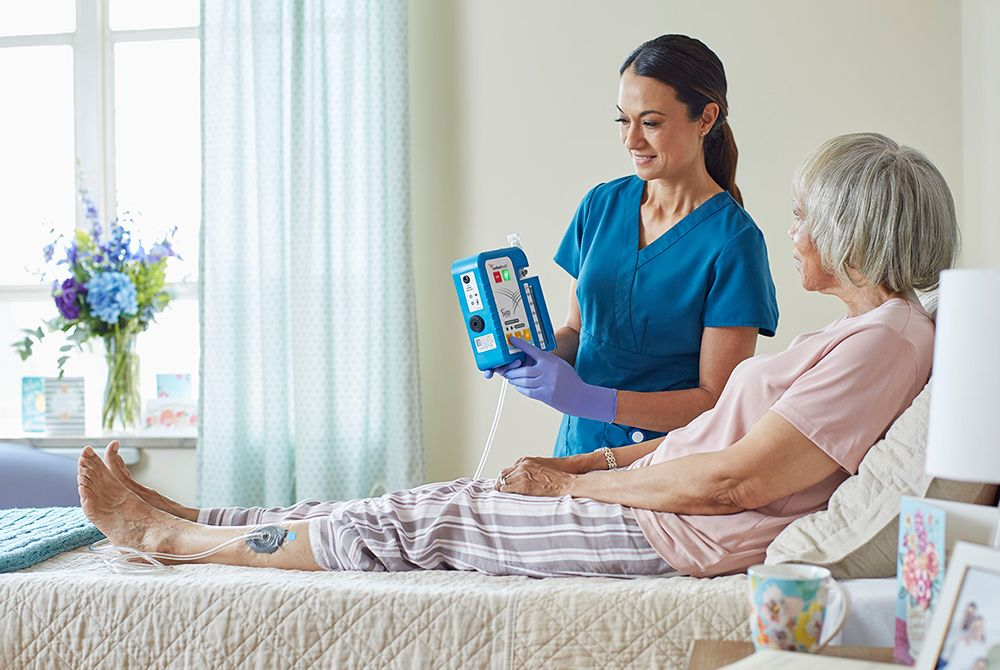 Nurse giving instructions on the Cardinal Health™ SVED® to a patient in bed.