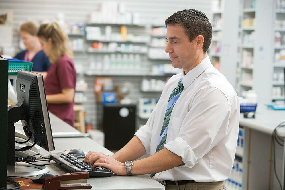 pharmacist inside pharmacy placing order on computer
