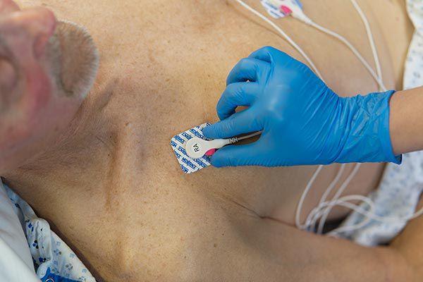 Nurse placing an electrode on a patient.