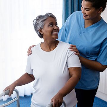 Nurse helping patient with a walker.