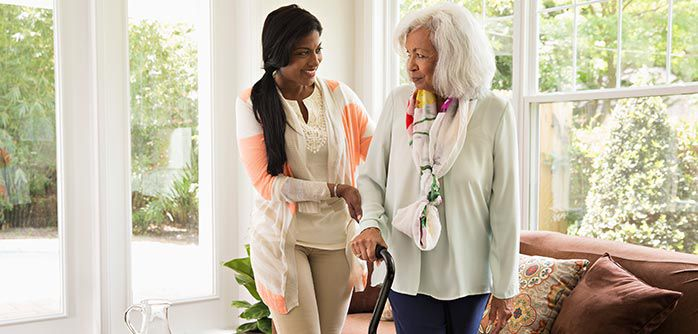 Home healthcare worker helping a patient with a cane.