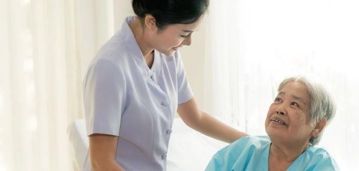 Medical professional with her arm on a patient's shoulder.