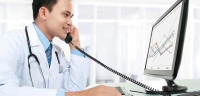 Doctor with a stethoscope around his neck talking on the phone while looking at a computer monitor.