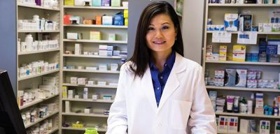 Smiling pharmacist sorting pills into the Dispill® Medication Packaging System.