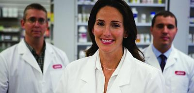 Smiling pharmacist standing in front of shelves of pharmaceuticals.