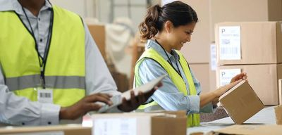 Distribution worker smiling while looking at a box.