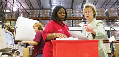 Distribution workers checking an order in a tote.