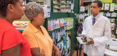 Pharmacist showing two patients a product.