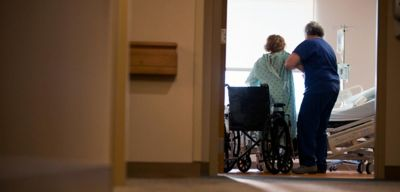 Nurse helping a patient out of her wheel chair.