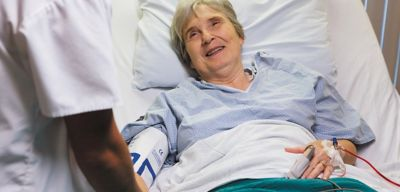 Nurse holding patient's hand.