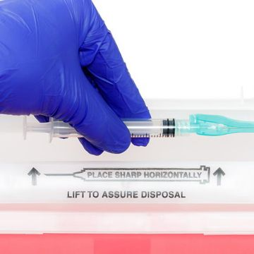 Disposing of a used needle in a sharps disposable container.