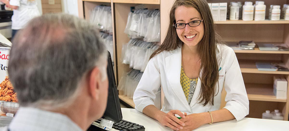 Pharmacist talking to patient behind counter.