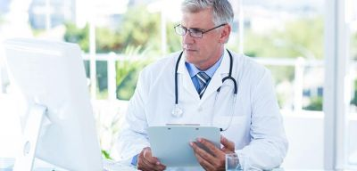 Doctor looking at his computer monitor while holding a clipboard.