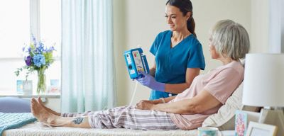 Nurse demonstrating the SVED NPWT device to a patient.
